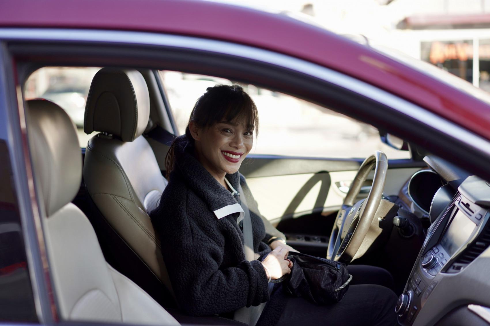 girl smiling in her car.